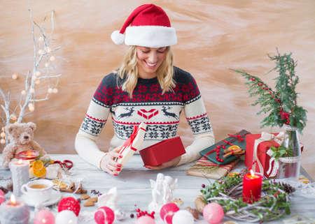 prepare: Happy woman wrapping Christmas present box