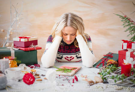 Mujer deprimida con el desorden de regalo de Navidad