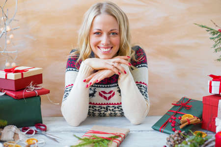 prepare: Happy woman sitting by the table and preparing gifts for Christmas celebration
