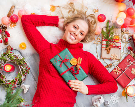 clothes interesting: Happy woman lying on the floor with gift box in hand Stock Photo