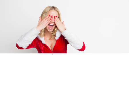 christmas spirit: Woman in red Christmas costume covering her eyes