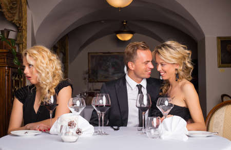 threesome: Annoying sweet couple getting on their friends nerves Stock Photo
