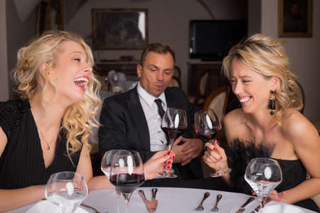 third wheel: Two females having a fun conversation while man is bored Stock Photo