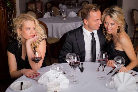 Женщина скуку во время ужинал с парой Фото со стока