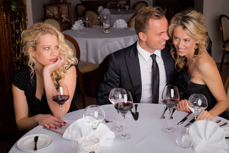 third wheel: Woman being bored while having dinner with couple
