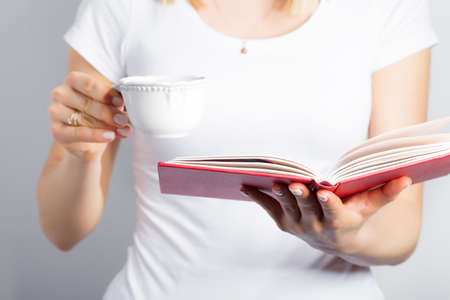 open hands: Woman with coffee cup and book in her hands