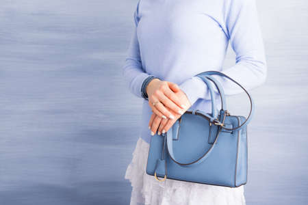 Woman holding blue purse Stock Photo