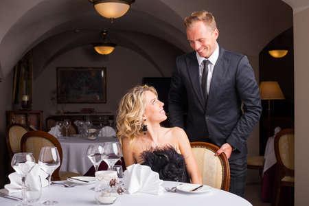 Człowiek jest dżentelmenem i pomagając kobieta na krześle