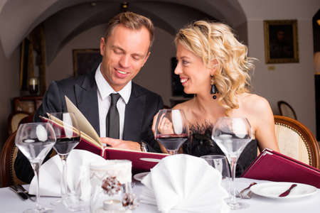 what to eat: Couple at restaurant choosing what to eat from menu