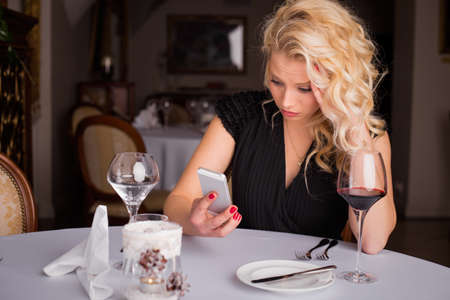 sexy girl sitting: Woman at restaurant looking at her phone