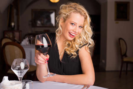 wine and dine: Happy woman with wine smiling