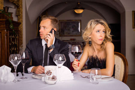 bore: Man talking on the phone while he is on date Stock Photo