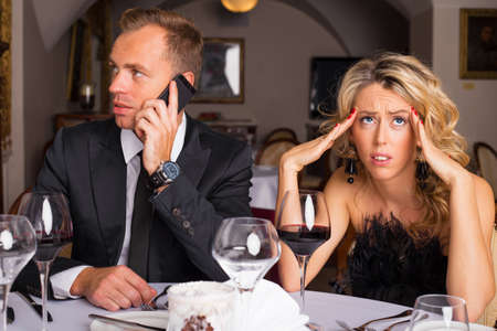 bored man: Woman at dinner date being annoyed of man talking on the phone Stock Photo