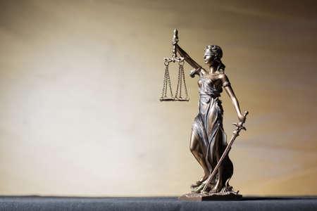 balanza de la justicia: Themis figura sobre fondo marrón Foto de archivo