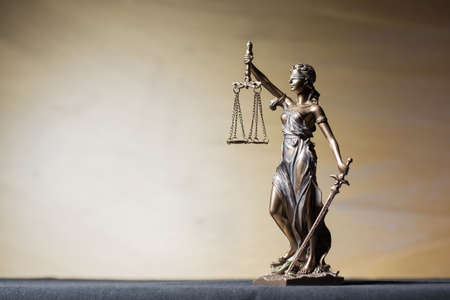 balanza de la justicia: Themis figura sobre fondo marr�n Foto de archivo