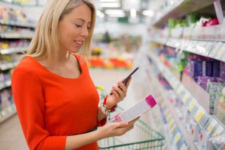 compare: Woman using smartphone to compare prices in supermarket Stock Photo
