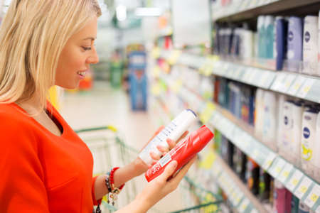 choosing: Woman in supermarket comparing two products