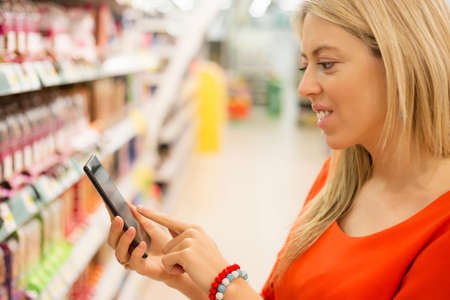super market: Woman in supermarket checking prices on her smartphone