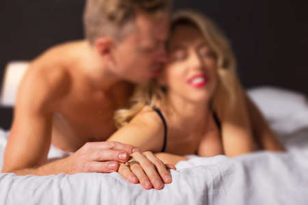 sex on bed: Woman and man making love