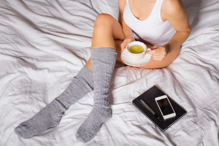 girl home: Woman sitting in bed with cup of tea Stock Photo