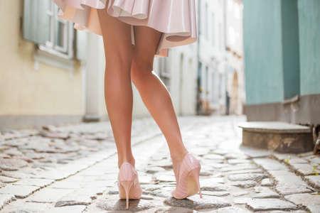 modelo desnuda: Señora atractiva con las piernas hermosas caminando en el casco antiguo Foto de archivo