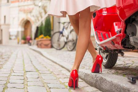 tacones rojos: Mujer con tacones altos de pie junto a la elegante scooter de moto roja Foto de archivo