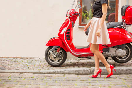 red shoes: Lady in front of red moto scooter Stock Photo