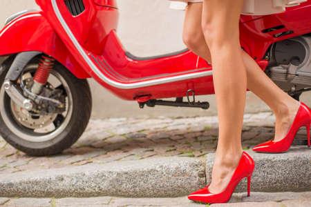 tacones rojos: Mujer con los zapatos de tacón rojo y scooter de color rojo brillante