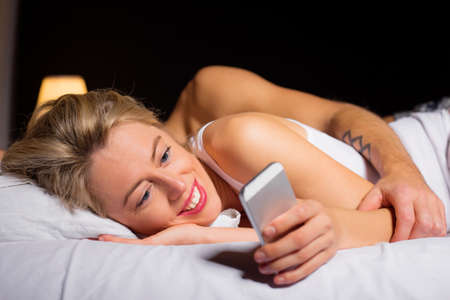 Woman texting someone while boyfriend is asleep