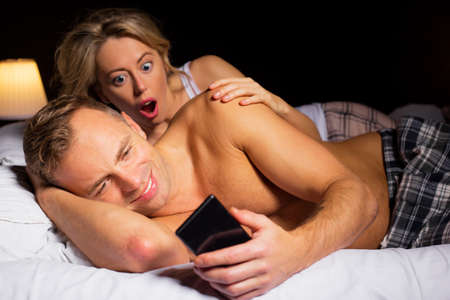 cheating: Surprised woman caught her man cheating Stock Photo