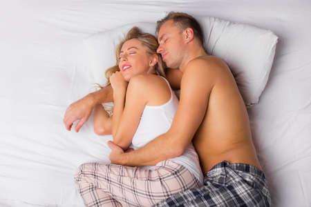 couple au lit: Heureux couple de couchage et câlins