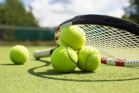 Tennisbälle und Schläger auf dem Rasenplatz Lizenzfreie Bilder