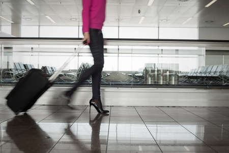 Woman walking in airport, blurred in motion