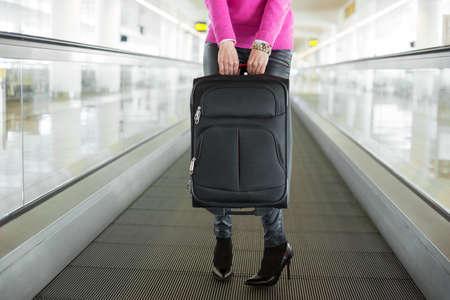 mujer con maleta: Mujer que sostiene la maleta en el aeropuerto Foto de archivo