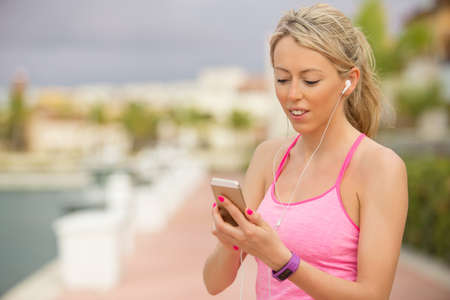 Sporty fit girl using smartphone outdoors