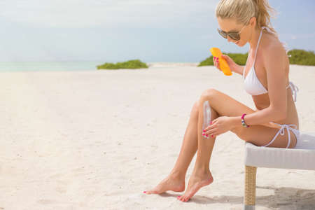 sun beach: Woman sunbathing in bikini and applying sunscreen Stock Photo