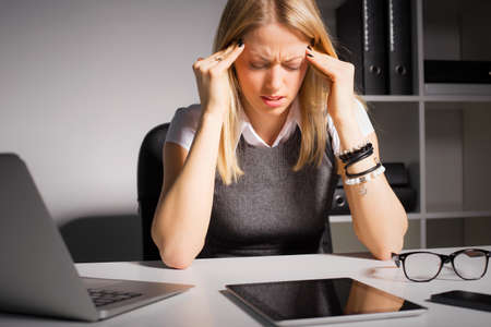 stress: Woman holding her head in pain