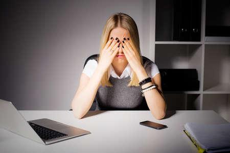 agotado: Mujer que se sienta en su oficina con sus ojos cubiertos