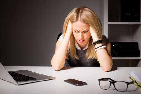 disgust: Woman in office holding her head in disgust