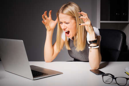 Woman looking at computer and going crazy