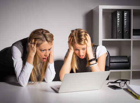 hands work: Two female coworkers looking at computer and holding their heads in shock Stock Photo