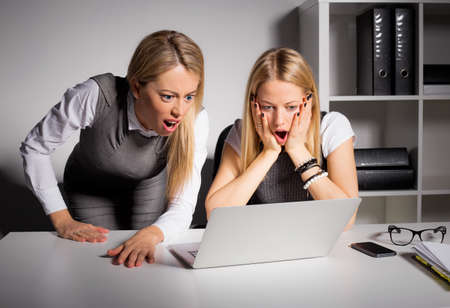 coworkers: Co-workers looking at computer in shock