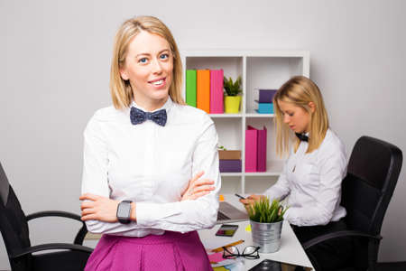 casual office: Women working in office standing with crossed hands Stock Photo