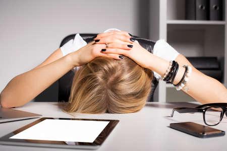 agotado: Mujer de negocios cansado que se reclina la cabeza sobre el escritorio