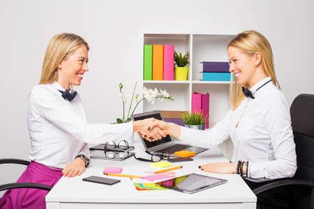 cerrando negocio: Dos mujeres de negocios de cerrar el trato con apret�n de manos Foto de archivo