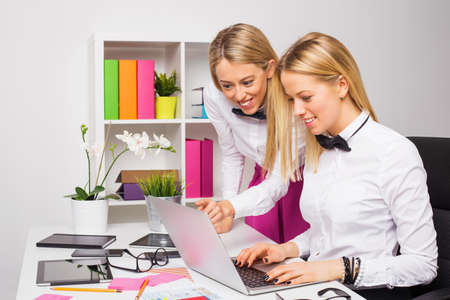 training device: Two female co-workers working as a team on laptop Stock Photo