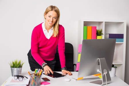 casual office: Woman standing in by the desk in office