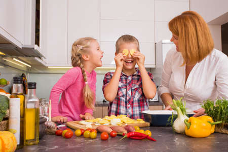 niños cocinando: Familia que se divierte en la cocina Foto de archivo