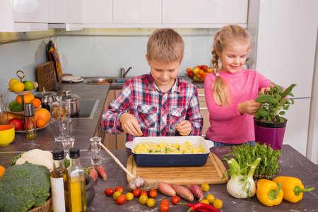 siblings: Siblings cooking in kitchen Stock Photo