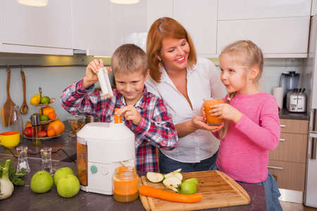 making: Mother, son and daughter making fresh juice in kitchen